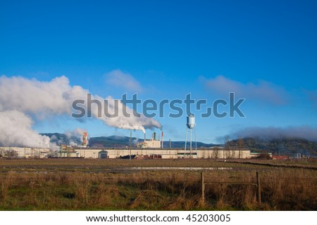 A paper mill in Oregon emits smoke and pollution into the clean air and blue sky overhead.
