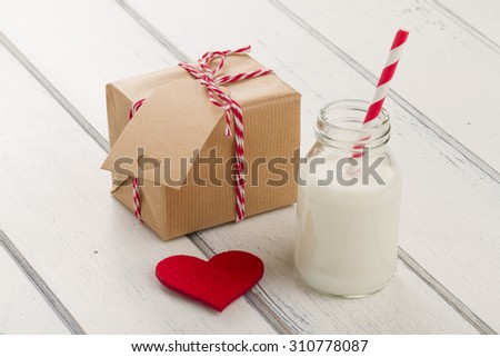 A paper parcel (christmas gift box) with a tag wrapped with paper kraft and tied with red & white baker\'s twine. A red heart and a school milk bottle with a straw drink on a white wooden table
