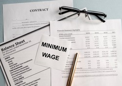 a paper with MINIMUM WAGE text on backgrounwith documents and glasses