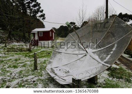A parabolic antenna on a grass field is seen covered in snow during winter season in Sao Joaquim, Santa Catarina state, Brazil. #1365670388