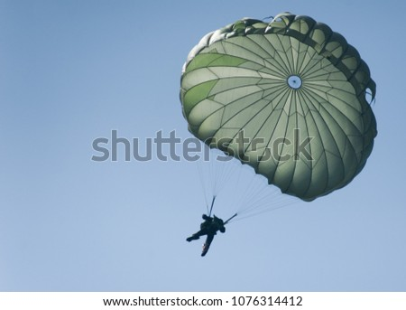 A parachute during a risky operation at sea. A special forces paratrooper jumping from a plane.