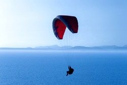 A paraglide flying gliding on a clear blue sky at the golden hour with a nice wind windy breeze on a sunny day