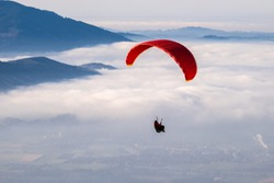 a paraglider above the clouds