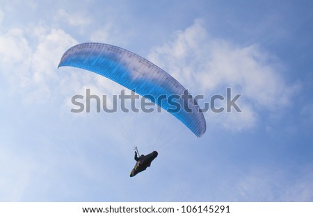 A paraglider against a clear blue sky