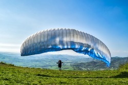 a paraglider launching from the edge of mountain in Lombardia region in italy