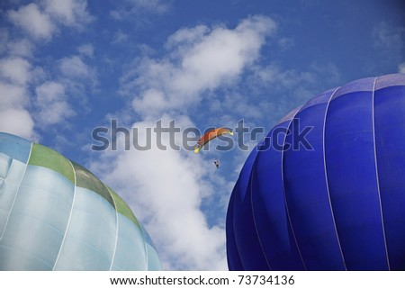 A paraglider making a risky move to fly between two hot air balloons during a hot air balloon festival.