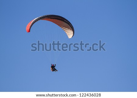 A paraglider takes to the sky. Shot from below against a blue sky.