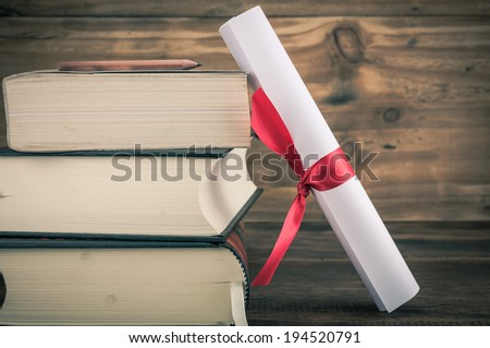 A parchment diploma scroll, rolled up with red ribbon beside a stack of books on wood background with vintage filter