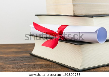A parchment diploma scroll, rolled up with red ribbon on stack of book on wood background