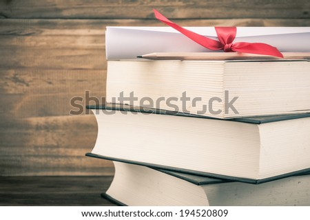 A parchment diploma scroll, rolled up with red ribbon on stack of book on wood background with vintage filter