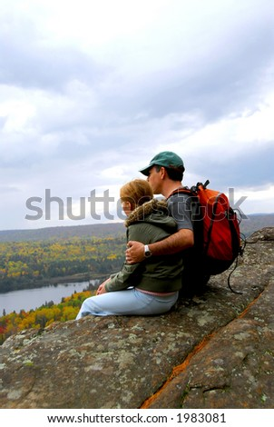 A parent and a child sitting on a cliff edge enjoying scenic view