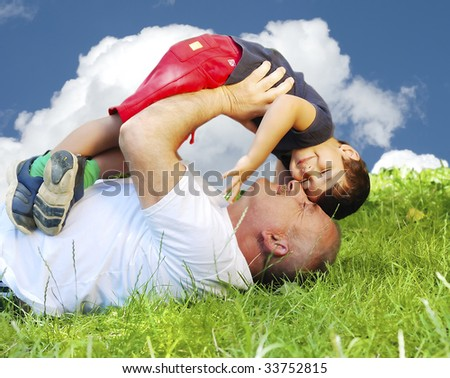 A parent and his kid laying and smiling on grass