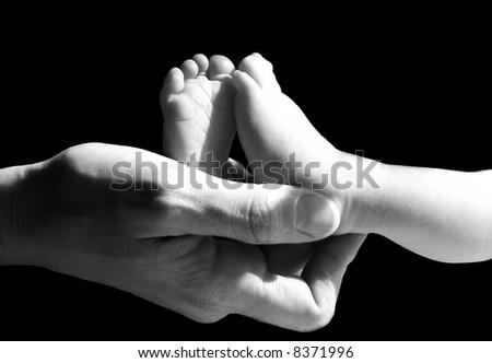 A parent holding a newborn baby's feet