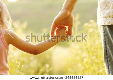 Stock Photo a parent holds the hand of a small child