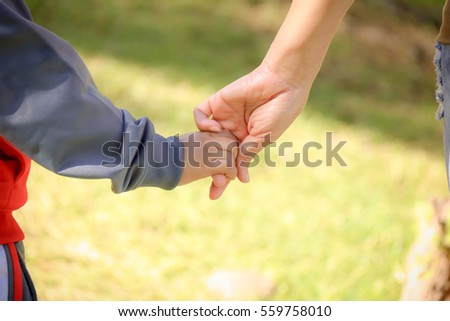 a parent holds the hand of a small child. Love and bond between mother and child.