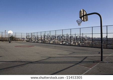 A park basketball court in Jersey City, with the New York skyline visible behind.