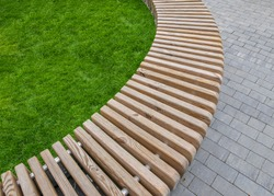 A park bench in the form of a curved row of smooth wooden blocks