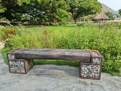 A park bench made of large planks There is a grate to put the stones supporting both ends.