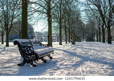 A park bench on a snowy day. Photo taken at Greenwich in London #1261796635