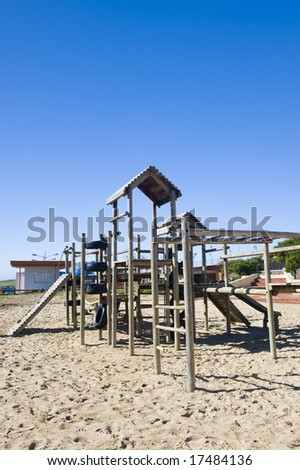 A park next to the beach with a play area for kids containing a wooden jungle-jim.