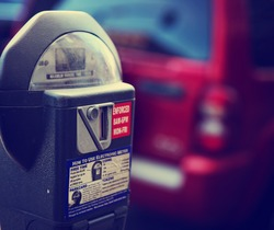 a parking meter with a car in the background on a city street downtown toned with a retro vintage instagram filter app or action effect