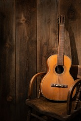 a parlor guitar resting on a vintage saloon chair against darkened barn wood. Dramatic lighting for mood with room for text