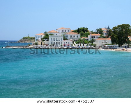 A part of Spetses island town, Greece; traditional houses, a small beach, and a lighthouse can be seen