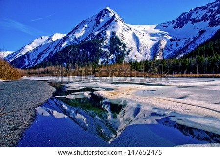 A Partially Frozen Lake With Mountain Range Reflected In The Partially Frozen Waters Of A Lake In The Great Alaskan Wilderness. A Beautiful Landscape Of Blue Sky, Trees, Rock, Snow, Water And Ice.