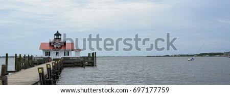 A partially submerged sailboat sits on the bottom of Shallowbag Bay off the Roanoke Marshes Lighthouse in Manteo North Carolina #697177759