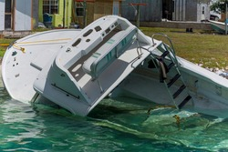 A partially sunk boat by the coastline of a harbor area at Alice Town, Bimini.