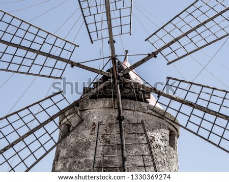 a particular close shot of an old windmill located in the salt pans of