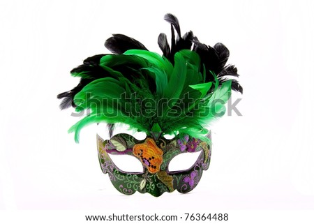 A party mask decorated with green and black feathers that can be worn at a masked ball.