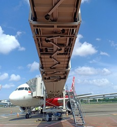 A Passenger Boarding Bridge (PBB) (also known as an air bridge, jet bridge, jetway, and sky bridge as well as by other terms) is an enclosed, elevated passageway which extends from an airport terminal