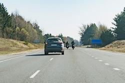 A passenger car overtaking motorcyclists on the highway