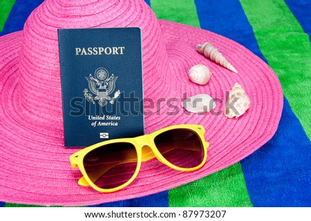 A passport on a pink tourist hat with yellow sunglasses and sea shells - stock photo
