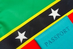 A passport stands against the flag of Saint Kitts and Nevis. The concept of travel and tourism.