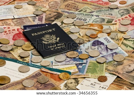 A Passport with ticket stubs on top of mixed foreign money including US, Taiwan, Indian, Hong Kong, Honduran, Malaysian and Korean currency