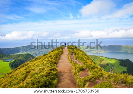 A path leading to viewpoint Miradouro da Boca do Inferno in Sao Miguel Island, Azores, Portugal. Amazing crater lakes surrounded by green fields and forests. Tourist at the end of the scenic way.