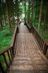 A path made of wooden flooring with a railing in the forest.