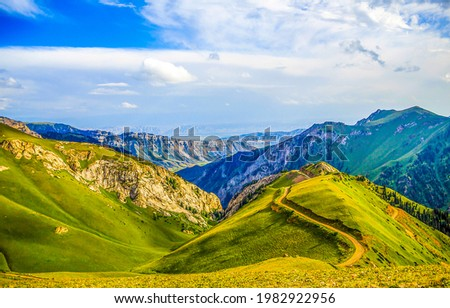 A path on a green hilltop in the mountains. Mountain green hill valley panorama. Mountain landscape
