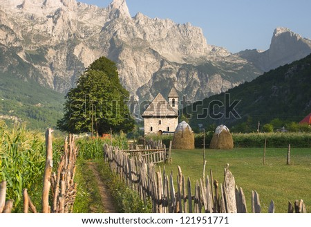 a path with wooden fence leads the catholic church in the Theth Valley, on background the mountains of Albanian Alps