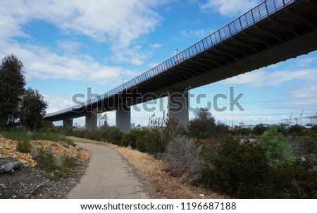 A  Pathway Curving Next To a Roadbridge High above. #1196687188