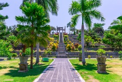 A pathway leading to the stairs of a palace in the garden at Ujung Water Palace (also known as Ujung Park or Sukasada Park) with tropical trees, manicured lawns and ornamental pots in Bali, Indonesia