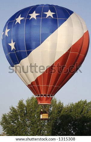 A patriotic hot air balloon lifts off into the blue sky