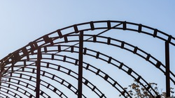 A pattern of curved steel structures against a blue sky. Construction of an arched metal canopy. Architectural construction. The metal arches. Repeating drawing. Welded elements.