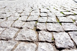 A paved area of grey cobblestones classically laid with joints of earth and green vegetation in places, everything in the close-up