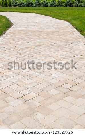 A paved walkway with green grass