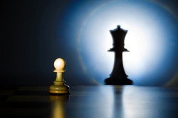 A pawn on a chessboard looks at its shadow of the future queen