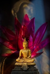 """A peaceful superimposed and double exposure images of Golden Buddha statue from Wat Pathum Wanaram, Bangkok, Thailand and a pink lotus. Buddha statue is posing """"The attitude of subduing Mara"""