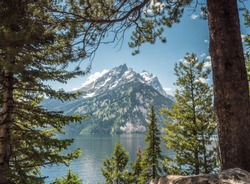 A peak of the Grand Teton mountain range, set upon the stills waters of Phelps Lake, Grand Teton National Park, Wyoming, USA. The snow dappled mountain is framed by the green pine forests.
